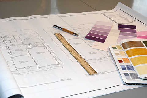 Drafting material including a ruler, pencil, and swatches for a floor plan