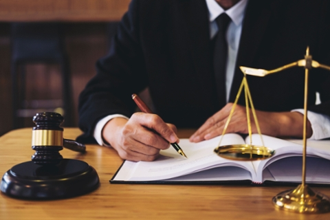 An individual holding a pen with a gavel and scale on his table